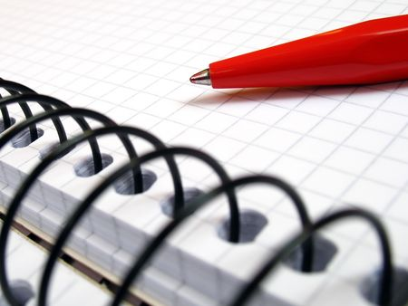 notebook with spiral and a red pen in close-up photo
