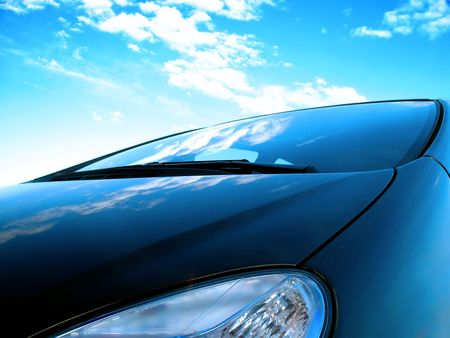 reflect: close up of a frontside of a car under a cloudy blue sky