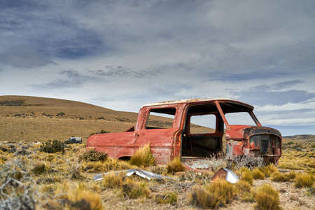 old red car wreck standing in the middle of nowhere in Patagonia in a vast landscape
