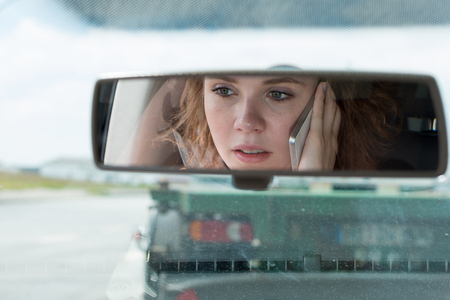 A young woman drives a car and talks on the phone Stock Photo