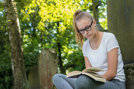 A young woman with glasses sits in a park and read a book Banco de Imagens - 110253902