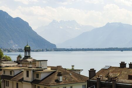 View over roofs at Geneva lake and the Alps in the background