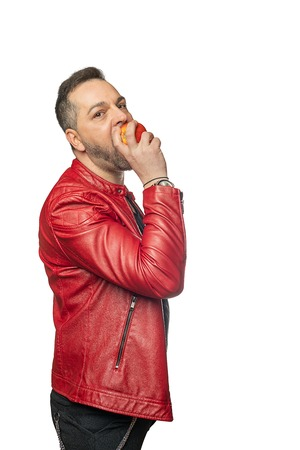A man in stylish clothes in front of white background bites into an apple and looks into camera