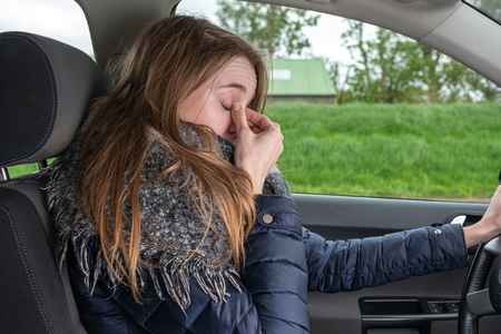 a woman driving overtired car and rubbing her eyes 스톡 콘텐츠