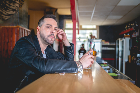 Man with a drink and a cigarette at a bar looks thoughtfully at the camera