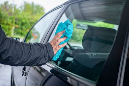 A person polishes the window on a car with a leather cloth