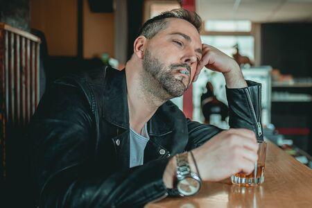 Ein Mann in einer Bar an der Theke schaut mit einem Whisky in der Hand und einer Zigarette in seinem Mund auf Standard-Bild