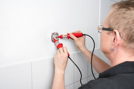 An electrician checks a socket outlet with a voltage detector 写真素材