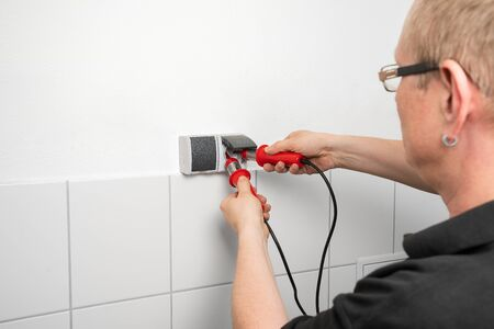 Electrician checks a socket outlet with a voltage indicator