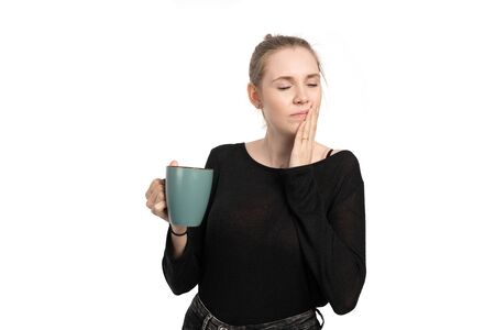 a young woman is sensitive when drinking hot drinks and get toothache