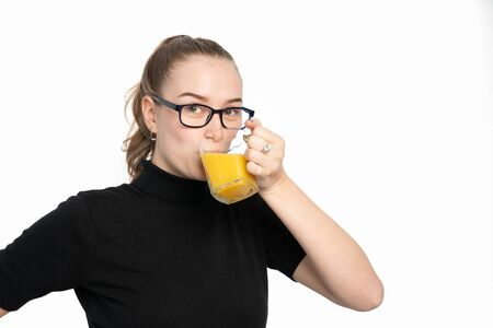 studio shot of young woman hold a glass of orange juice and drinks Stock Photo
