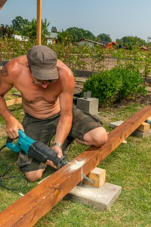 a handyman saws through a beam with an electric saw