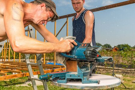 a handyman saws a wooden beam with a circular saw