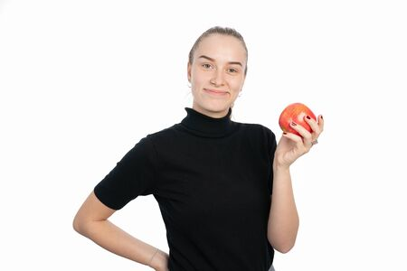 A young woman is holding an apple in her hand and smiling