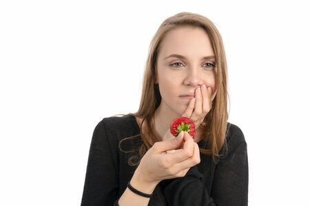 Young woman is pain sensitive when eating sweet strawberry Banque d'images