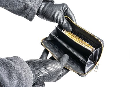 A burglar with gloves tries to steal money from a purse 写真素材