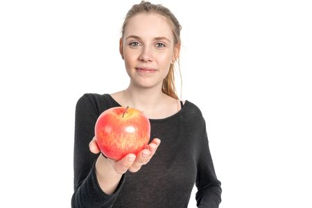 A young woman is holding an apple in her outstretched hand and smiling