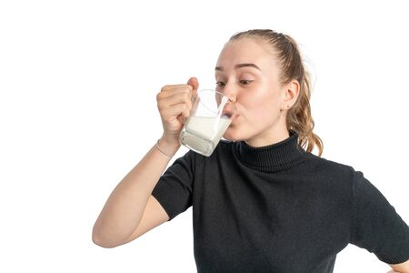 A studio shot of a young woman hold a glass of milk and drinks