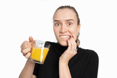 Une jeune femme est sensible à la douleur lorsqu'elle boit des boissons froides