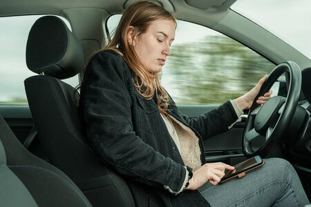 A young woman is typing on a mobile while driving a car
