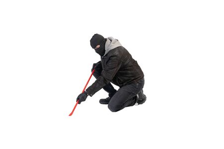 burglar knee with crowbar and mask against a white background
