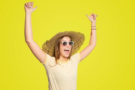 young woman with summer hat and sunglasses is raising her arms in joy Stock Photo