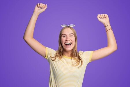 young happy woman is raising her arms in joy