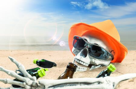 skeleton of a celebrating person died of too much alcohol on a lonely beach