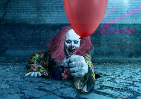 a scary clown with a balloon rising from the sewer