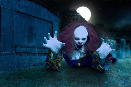 a scary clown lies in front of a gravestone and makes a frightening gesture