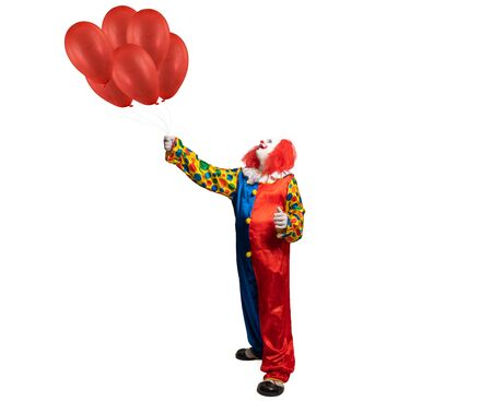 a clown holds red ballons in his hand
