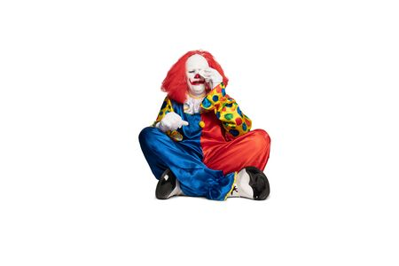 sad clown sitting on the floor and crying
