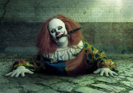 killer clown with a knife in the mouth rising from the sewer