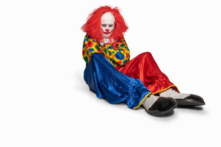 sad clown sitting on the floor isolated background
