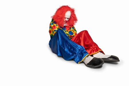 sad clown is sitting on the floor looking down Stock Photo
