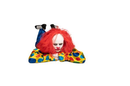 bored clown lies on the floor and looks at the camera