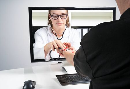 Concept of remote medical examinations. A doctor makes a remote examination on a patients home through the monitor