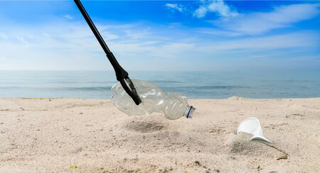 concept about pollution collecting plastic garbage with tongs on a beach 版權商用圖片