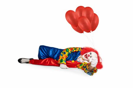cheerful clown lies on the floor holding balloons in his hand 스톡 콘텐츠