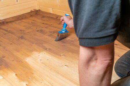 man with a brush seals a wooden floor with a glaze 写真素材