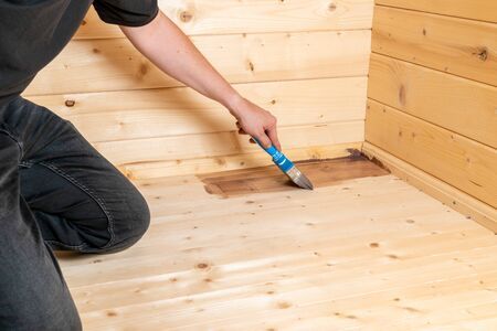 man seals a wooden floor with a glaze and a brush