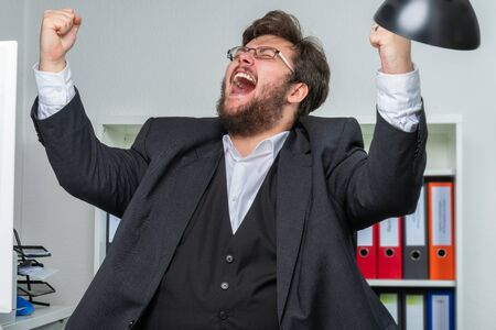 A person in an office bursts out in jubilation and pulls his arms up in the air Imagens