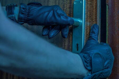 A burglar carefully opens a flat door with his hands inside the flat