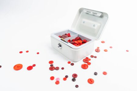 Many red buttons lie in an open petty cash and around Stock Photo