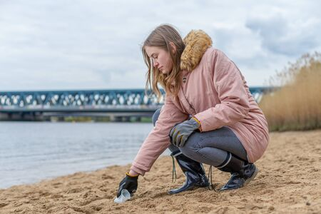 a young woman is cleaning the beach from plastic waste by hand