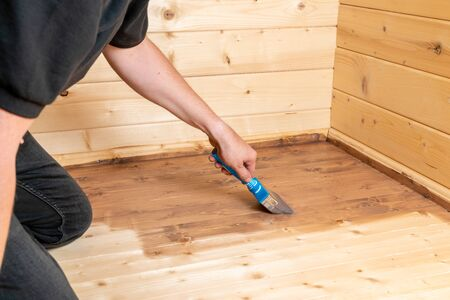 a man paint a wooden floor with a glaze and a brush