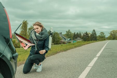 A young woman with a car breakdown tries to assemble the warning triangle
