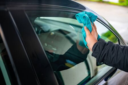 A person polishes the window on a car with a leather cloth Stock Photo