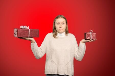 A young woman holds two gifts in her hand and can not decide for one