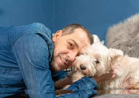 A man cuddles with his dog on the couch